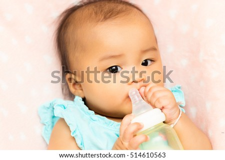 Asian baby infant eating milk from bottle, 5 months after birth