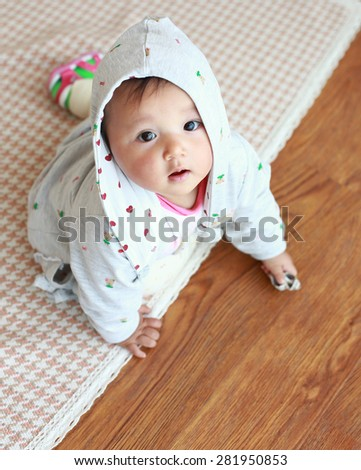 Asian baby lying on the floor