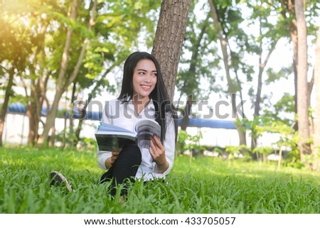 Asian  Beautiful smiling woman reading book in park summer