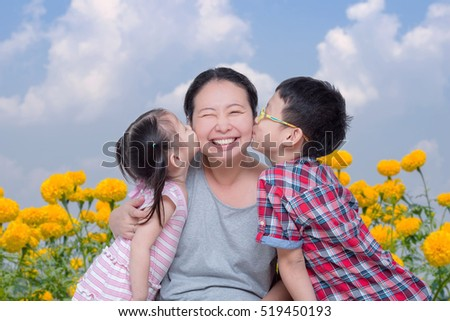 Asian boy and girl kissing their mother in park