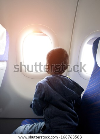 asian boy looking outside of airplane window