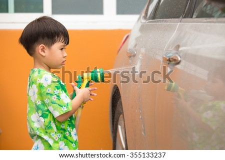 asian boy spraying water to wash a car