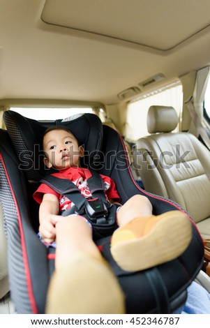 Asian boy wearing red T-shirt in safety car seat. Unhappy child.