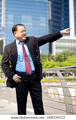 Asian business man in suit pointing to a direction