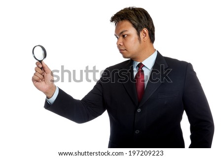 Asian businessman look through a magnifying glass isolated on white background