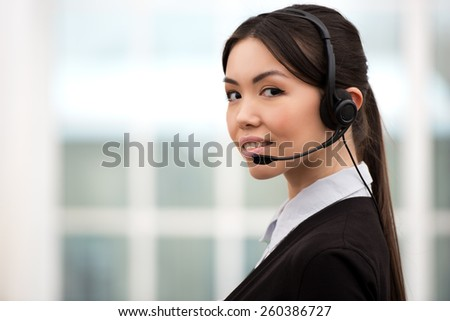 Asian call center female operator looking at camera with headphones. Office interior with window