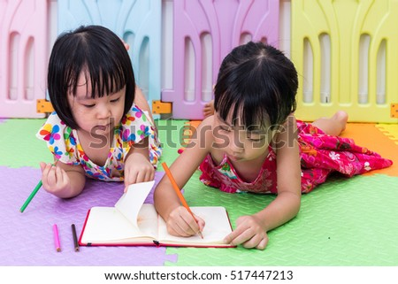 Asian Chinese little sisters laying on the floor coloring at home