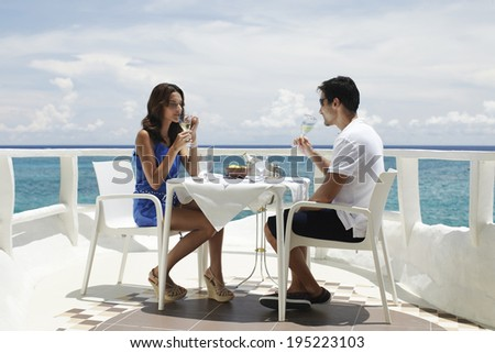 Asian couple drinking wine by the sea