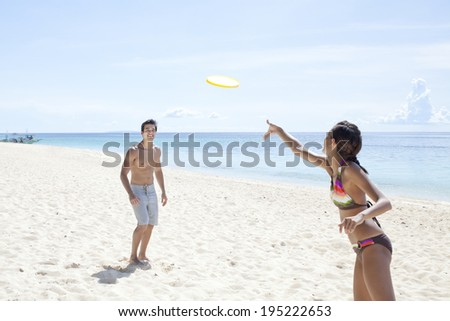 Asian couple playing Frisbee at the beach in Boracay in Philippine