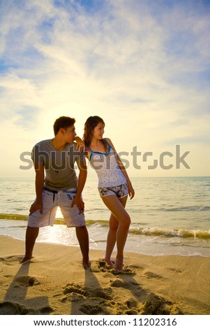 asian couple standing by the romantic golden sunset beach