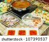 Asian dishes - tomyam steamboat set with various ingredients and spicy dipping sauce - stock photo