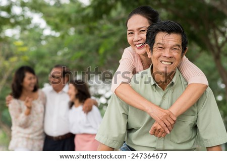 Asian elderly couple piggybacking outdoors
