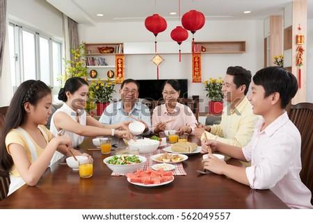 Smiling woman serving family dinner tet stock photo for Japanese eating table