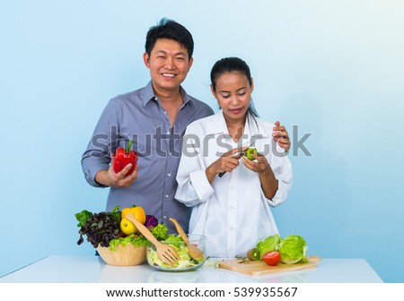Asian family making salad in kitchen