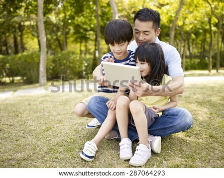 asian father and two children sitting on grass looking at tablet computer, outdoor in a park.