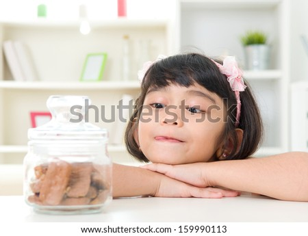 Asian girl looking at cookies inside the glass bottle