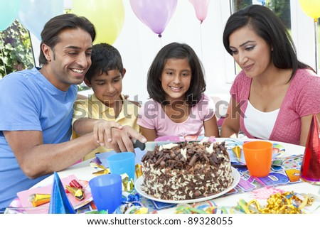Asian Indian family, mother, father, son & daughter celebrating a birthday party cutting the cake