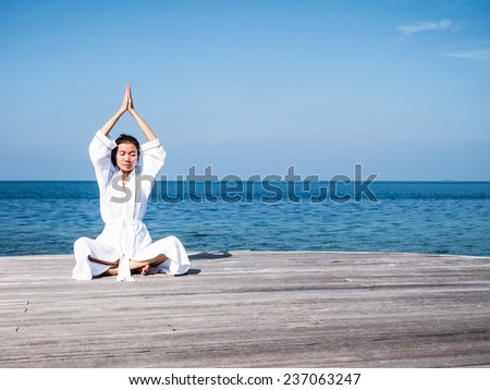 Asian Lady practicing yoga with seascape