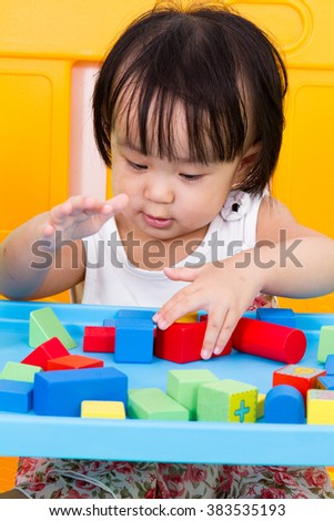 Asian Little Chinese Girl Playing Wooden Blocks at Home or Kindergarten