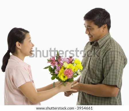 Asian man giving Asian woman a bouquet of flowers.
