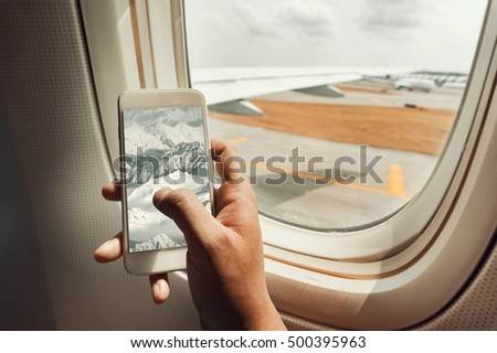 Asian man hand holding smart-phone on board of airplane near window seat and wing