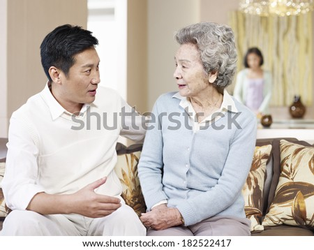 asian mother and adult son chatting on couch