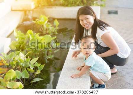 Asian mother and child having fun time at outdoor in sunset during vacations.