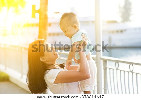 Asian mother and son having fun at outdoor in sunset during vacations.