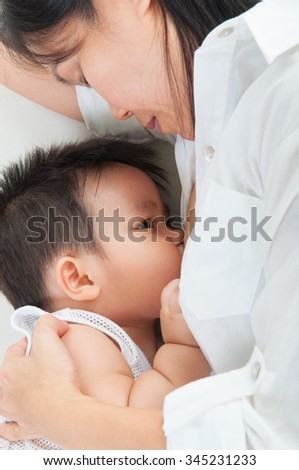 Asian mother breastfeeding her baby boy