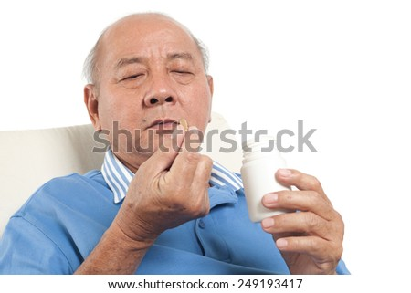 Asian senior man putting pills into mouth. Isolated on white background.