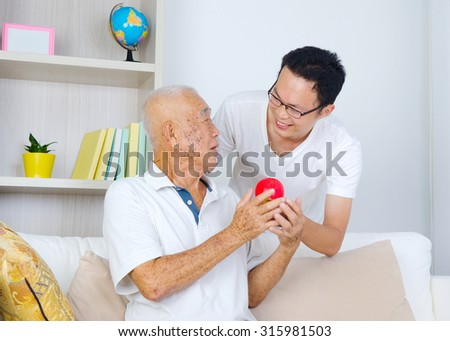 Asian senior man talking with his son while holding an apple