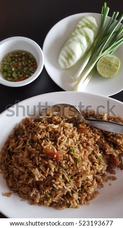 Asian-style braised pork belly with soy sauce fried rice, served with sidedish fresh vegetables and a lemon slice and Thai chili fish sauce.