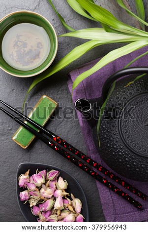 Asian sushi chopsticks, rose tea and teapot over stone table. Top view