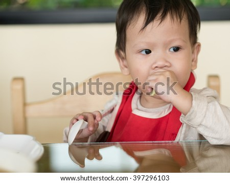 Asian toddler learn to eat meal herself.