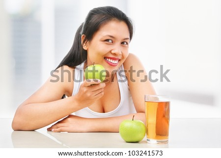 Asian woman holding a green apple and juice and another green apple in front of her