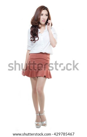 Asian woman holding mobile phone on white background.