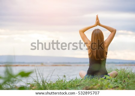 Asian woman is practicing yoga beside river