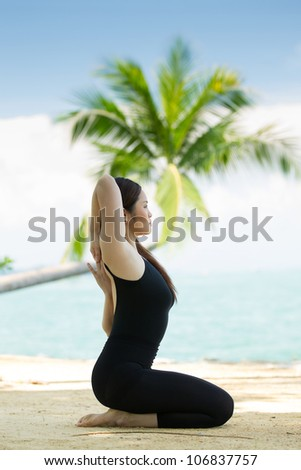 Asian woman practicing yoga by the sea