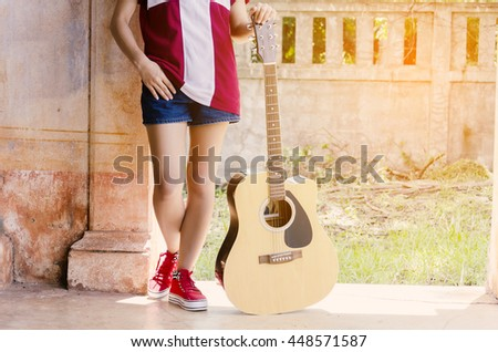 asian woman stand and has acoustic guitar in a morning with sunlight