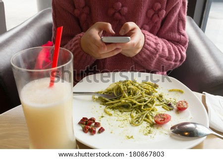 Asian woman text messaging during  meal in a restaurant