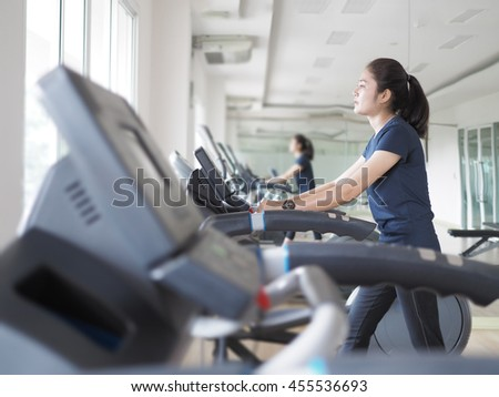 Asian woman walking,  running on treadmill gym workout.