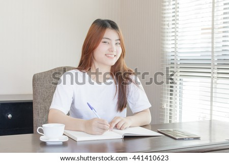 Asian woman working and smiling in office