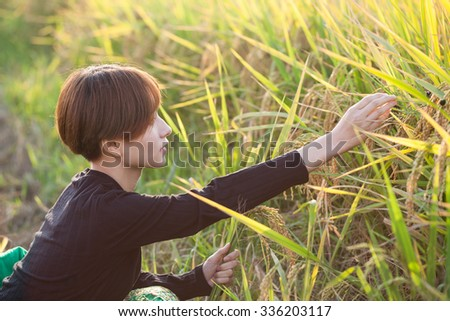 asian young female in the rice field in summer harvested field
