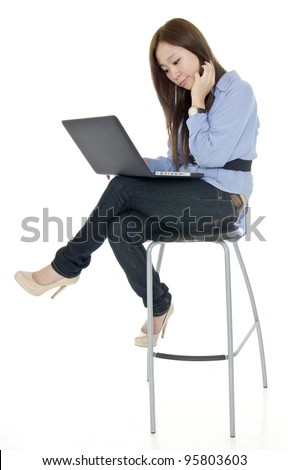 Asian young woman sitting on high chair while playing notebook.