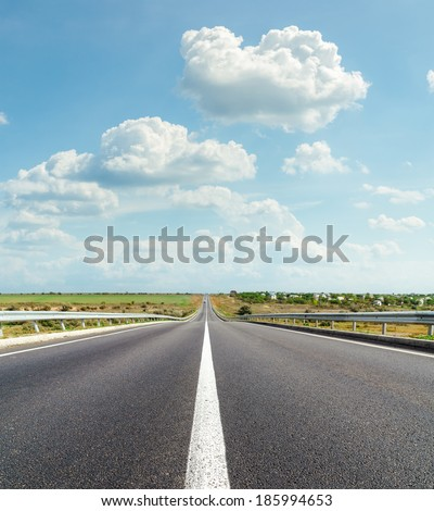 asphalt road and clouds over it