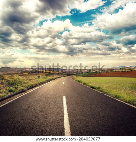 Asphalt road through green field over white cloudscape background.