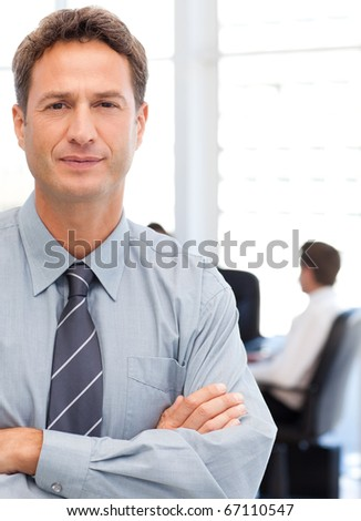 Assertive businessman standing in front of his team while working at a table in the background