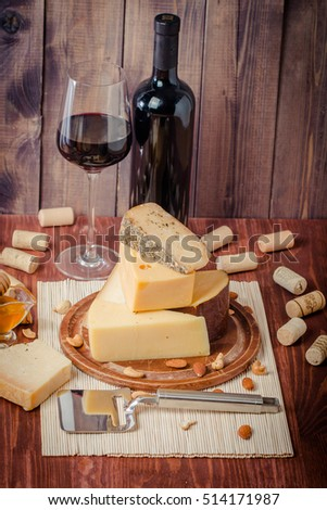 Assorted Cheese Plate with Red Wine, Nuts and Honey on wooden background