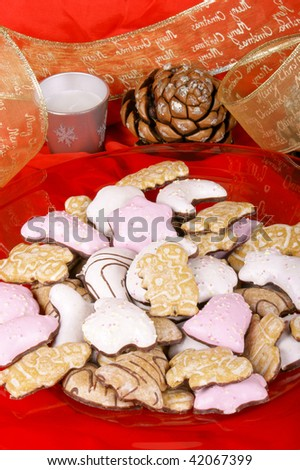 Assorted Christmas gingerbread cookies on a red plate and Christmas decorations over a red background