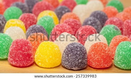 Assorted colored gum drops on a wood surface